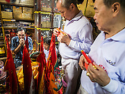 07 FEBRUARY 2014 - HAT YAI, SONGKHLA, THAILAND:   Men pray for a prosperous New Year in the back of a Chinese owned shop in Hat Yai. Groups of men go business to business with small altars and business owners make offerings and pray at the altars. Hat Yai was originally settled by Chinese immigrants and still has a large ethnic Chinese population. Chinese holidays, especially Lunar New Year (Tet) and the Vegetarian Festival are important citywide holidays.     PHOTO BY JACK KURTZ