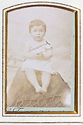 fading studio 1900s portrait of toddler wit golden passe-partout