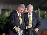 US President Bill Clinton admires an award given to him by Brian O'Dwyer, right, during a ceremony on the South Lawn of the White House September 11, 1998 in Washington, DC. Clinton received the Paul O'Dwyer Peace and Justice Award, an award named after Brian O'Dwyer's father, and established by the Emerald Isle Immigration Center, for Clinton's work in helping bring peace in Northern Ireland. The ceremony took place the same day the Starr Report was released to Congress.