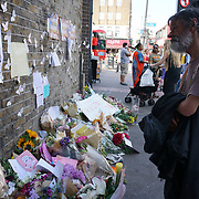 People bring floral tributes to the Finsbury Park in London on June 20, 2017 after a van attack in the area killed one and injured ten. Police are investigating the incident as an act of terror.