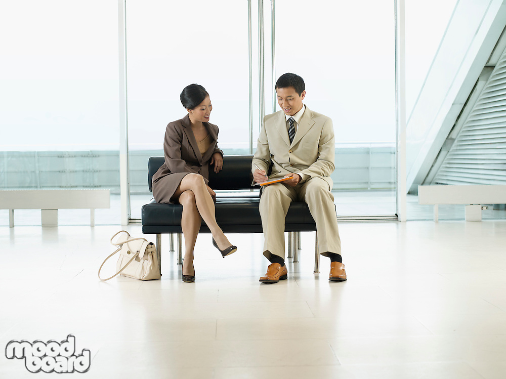 Businesspeople Sitting on Bench in airport looking over documents