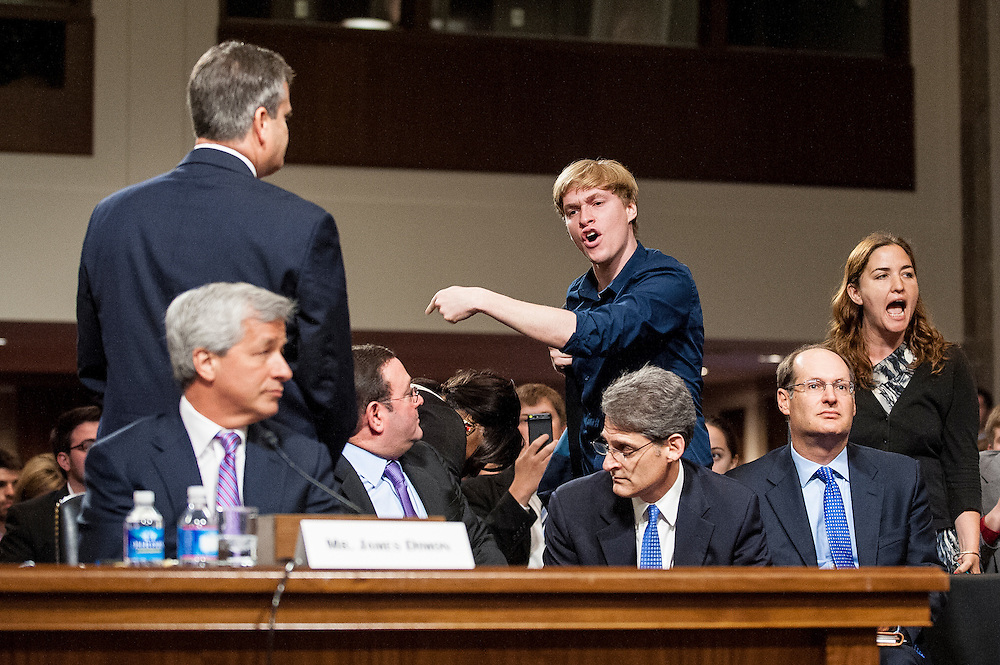 A protester yells at James Dimon, chairman of the board, president and CEO of JPMorgan Chase & Co., before he testifies before the Senate Banking, Housing and Urban Affairs Committee to explain a $2 billion trading loss in early May.