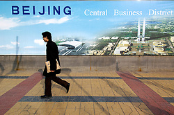 Man on street walking past billboard advertising the new Beijing Central Business District or CBD in Beijing China