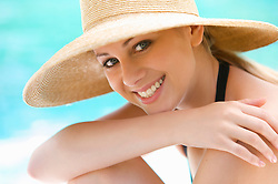 Close up of a smiling young woman wearing a straw hat