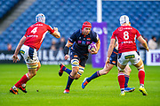 Grant Gilchrist (#5) of Edinburgh Rugby runs at Pierce Phillips (#4) and Dylan Hayes (#8) of SU Agen Rugby during the European Rugby Challenge Cup match between Edinburgh Rugby and SU Agen at BT Murrayfield, Edinburgh, Scotland on 18 January 2020.