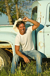 Man smiling and sitting on the rim of his pickup holding his cowboy hat