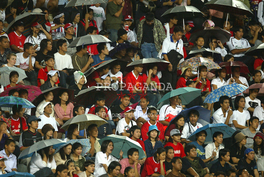 BANGKOK, THAILAND - Thailand. Thursday, July 24, 2003: Thai Liverpool fans try to keep dry during a preseason friendly match at the Rajamangala National Stadium. (Pic by David Rawcliffe/Propaganda)