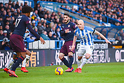 Aaron Mooy of Huddersfield Town (10) pressures Sead Kolasinac of Arsenal (31) and Alex Iwobi of Arsenal (17) during the Premier League match between Huddersfield Town and Arsenal at the John Smiths Stadium, Huddersfield, England on 9 February 2019.