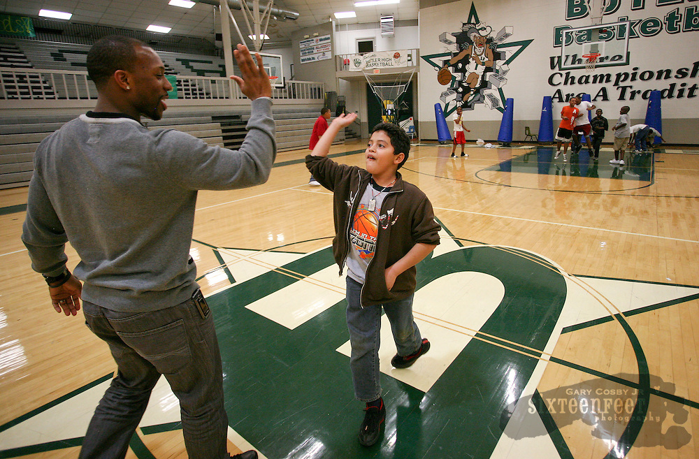 Photo by Gary Cosby Jr.   Ramzee Robinson works with children at Butler High School in the Huntsville Inner-City Learning Center Tuesday, February 21, 2012 in Huntsville, Alabama.  Robinson high fives Abimael Flores after Flores threw a touchdown pass during a pick up football game in the gymnasium. Robinson is a new member of the Denver Broncos.