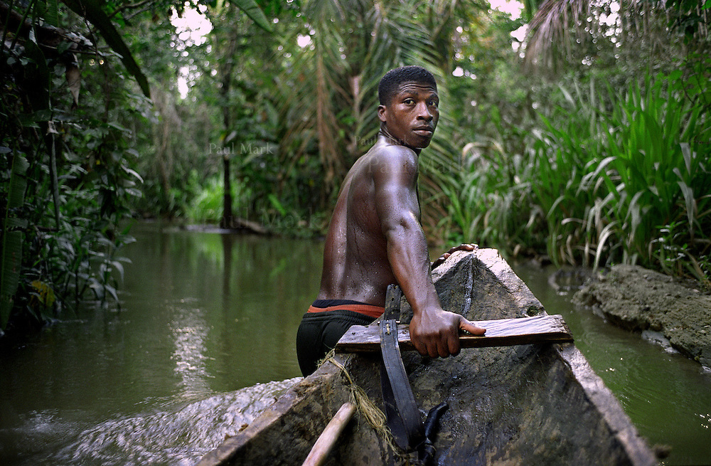 An afro-colombian farmer pulls a canoe through shallow river waters.