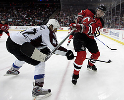 Feb 26, 2009; Newark, NJ, USA; New Jersey Devils defenseman Colin White (5) shoots the puck past Colorado Avalanche right wing Chris Stewart (42) during the third period at the Prudential Center. The Devils defeated the Avalanche 4-0.