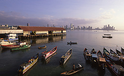 Wooden fishing boats moored at the Mercado de Mariscos (seafood market) on Bahia de Panama (Panama Bay) with the Panama City, Panama, CA skyline on the horizon.