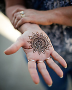 Kathy Kister, Pomeroy secretary, lets her fresh henna tattoo dry during the First Annual Multicultural Festival at Pomeroy Elementary School in Milpitas, California, on April 27, 2013. (Stan Olszewski/SOSKIphoto)
