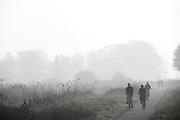 Een groep mensen fietst in de ochtend door de Waarderpolder.<br /> <br /> A group is walking in the early morning at the Waarderpolder.