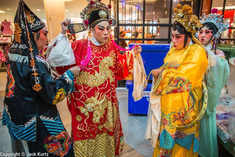 08 FEBRUARY 2013 - BANGKOK, THAILAND:  Chinese opera performers finish getting into their costumes and wait to go on stage for a Chinese New Year performance at Seacon Square in Bangkok. Chinese opera is popular in Thailand and is usually performed in the Teochew language. The weeks surrounding Chinese New Year are important for retailers in Thailand and many malls put on special promotions and events honoring Chinese culture, like Lion Dances or Chinese Opera. Thailand has a large Thai-Chinese population. Millions of Chinese emigrated to Thailand (then Siam) in the 18th and 19th centuries and brought their cultural practices with them.   PHOTO BY JACK KURTZ