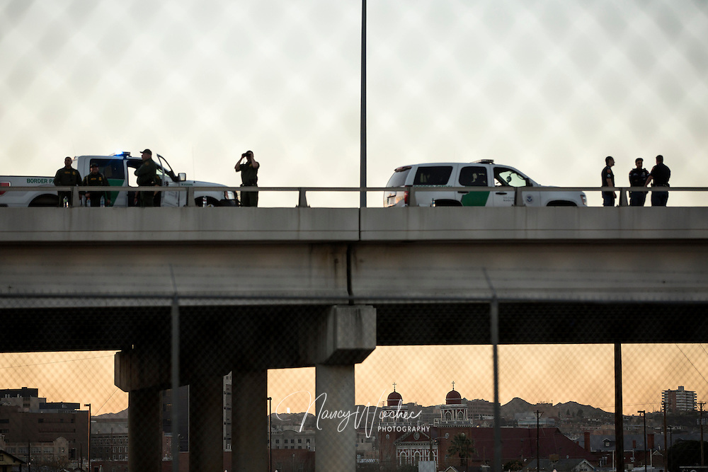 Officers with U.S. Customs and Border Protection survey the U.S.-Mexico border area from an overpass in El Paso, Texas, Feb. 17, as Pope Francis celebrates Mass nearby Ciudad Juarez. (CNS photo/Nancy Wiechec)