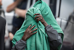 Licensed to London News Pictures. 20/10/2016. Croydon, UK. Migrants from the Calais jungle camp cover their faces as they arrive at the Home Office immigration centre in Croydon. British authorities are bringing over about 100 children this week to be reunited with their relatives. French authorities are expected to start dismantling the camp this week. Photo credit: Peter Macdiarmid/LNP