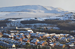 ©Licenced to London News Pictures. 08/12/17. Ebbs Vale, Wales,UK. Snow coming on the back of Storm Caroline, causes traffic disruption in South Wales. Here the houses of Dowlais, Merthyr Tydfil are dusted in white whilst the Ffos-y-Fran opencast spoil heaps loom behin,  large and white instead of their usual coal black.. Photo credit IAN HOMER/LNP