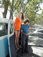Young woman standing in camper van door man looking at map at side of road