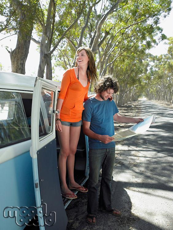 Young woman standing in camper van door man looking at map at side of road