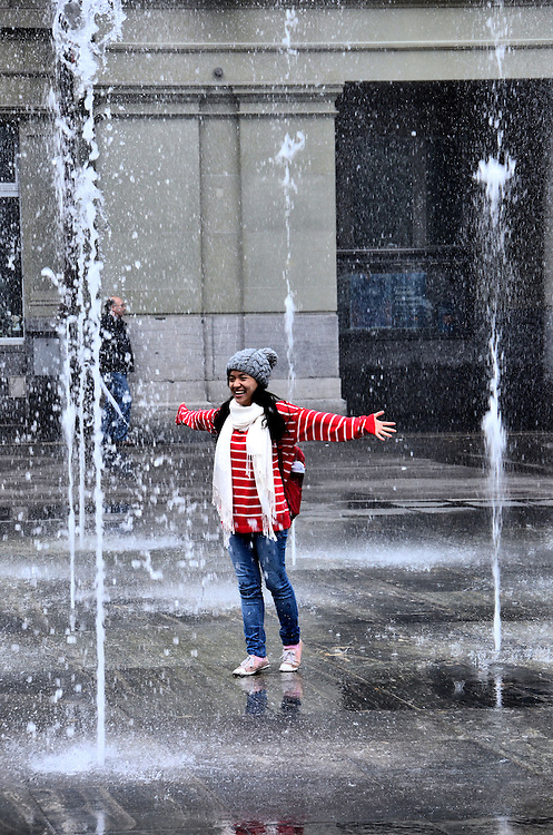 Young Woman Dancing in Federal Square Fountain in Bern, Switzerland <br /> This happy young woman skipping through the &ldquo;dancing waters&rdquo; of the 26 jet fountain in Federal Square, also called Bundesplatz, is in the heart of Bern&rsquo;s largest city square.  It faces the Federal Parliament building and the headquarters for Switzerland&rsquo;s central bank.  It is also the site of countless political rallies, concerts and a bi-weekly flower and produce market.