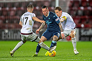 Miles Storey (#19) of Partick Thistle FC goes between Benjamin Garuccio (#17) and Christophe Berra (#6) of Heart of Midlothian during the William Hill Scottish Cup quarter final replay match between Heart of Midlothian and Partick Thistle at Tynecastle Stadium, Gorgie, Edinburgh Scotland on 12 March 2019.