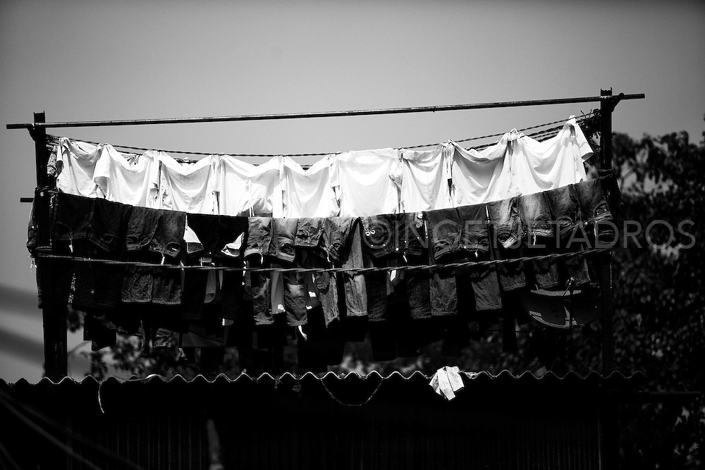 White linen drying on a clothes-line on a thin tin roof in Dhobi Ghat, open air laundry in Mumbai