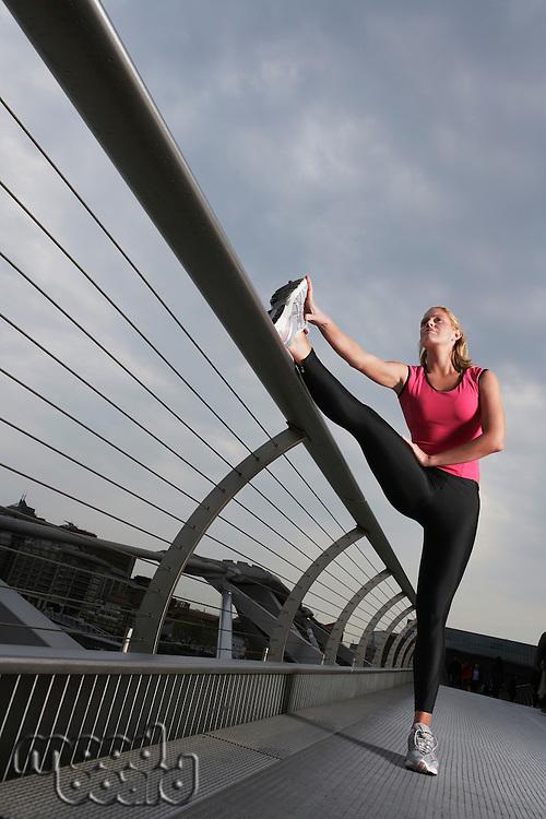 Woman stretching on foot bridge low angle view Millennium Bridge London England