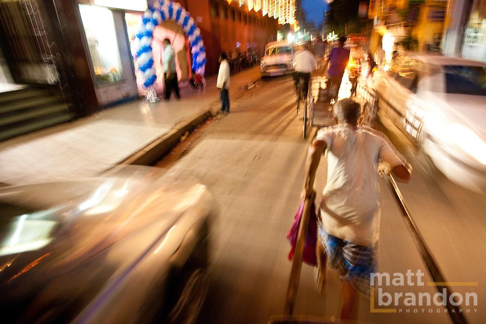 A rickshaw puller navigates the busy streets of Kolkata at night.