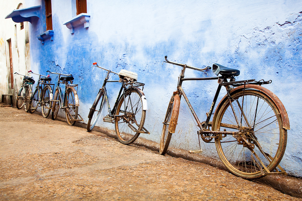 Five Bicycles Waiting Against A Blue Wall in Agra, India