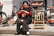 Woman sits knitting in Zi Zhong Road, old French Concession Quarter in Shanghai, China