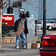 A homeless Vietnam Vet shows weariness at 22nd and Broadway in Denver, Colorado.  All his belongings are in the carboard box and the backpack sitting next to the traffic control box.