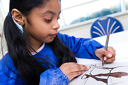 Young girl taking part in a craft activity at her local leisure centre,