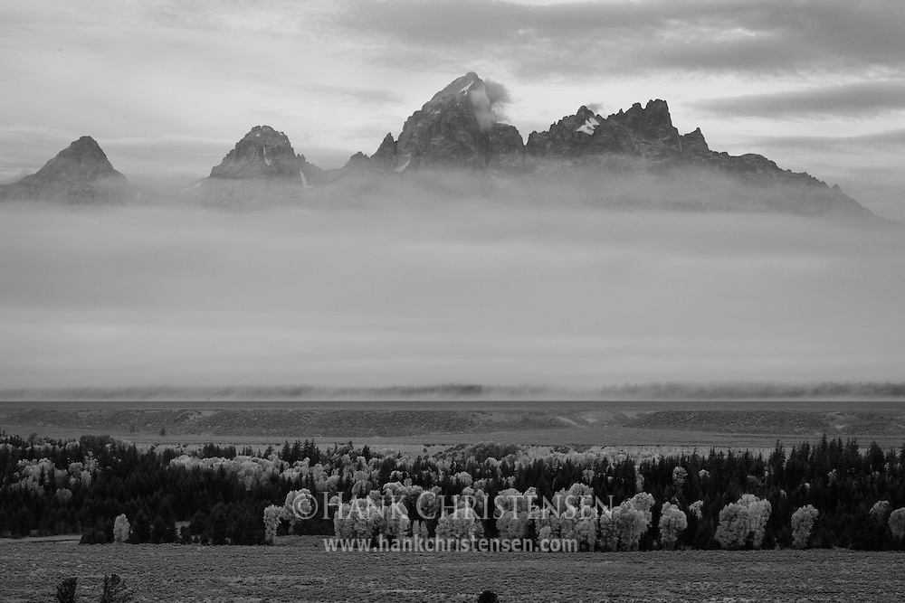 Thick fog and wildfire smoke fill the valley, obscuring the tetons at daybreak, Grand Teton National Park