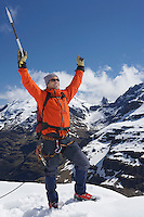 Mountain climber with arms raised on top of snowy peak