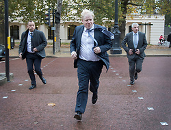 © Licensed to London News Pictures. 15/11/2017. London, UK.  Foreign Secretary Boris Johnson sprints across The Mall, followed by his close protection team,  as he heads to Whitehall ahead of a meeting with Richard Ratcliffe. Mr Ratcliffe's wife, Nazanin Zaghari-Ratcliffe, is currently serving a five-year prison sentence after being arrested at Tehran airport in April 2016 as she attempted to return home from a visit to see her family. Her sentence may be increased after Foreign Secretary Boris Johnson mistakenly said she was in Iran to train journalists. Photo credit: Peter Macdiarmid/LNP