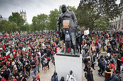 © Licensed to London News Pictures. 03/06/2020. London, UK. Members of the campaign group Black Lives Matter and supporters, gather in Parliament Square in central London and stand on the statue of wartime leader Winston Churchill to demonstrate, following the death of African American George Floyd while in police custody. The death of George Floyd, who died after being restrained by a police officer In Minneapolis, Minnesota, has caused widespread rioting and looting across the USA. Photo credit: Peter Macdiarmid/LNP
