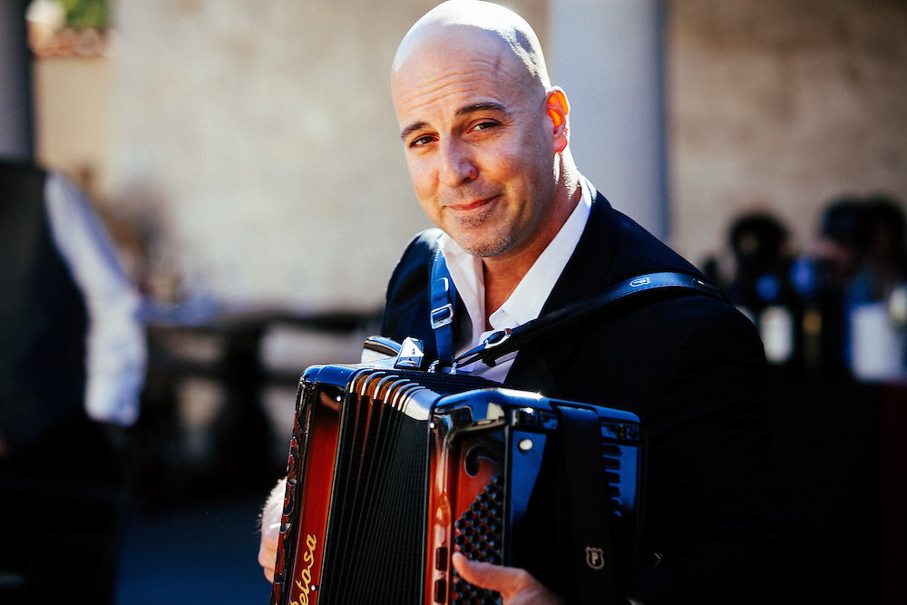 An accordion player entertaining guests during lunch in the piazza.