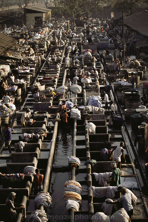 "Washing clothes at the Dhobi ghats, Bombay, India. The dhobi is a traditional laundryman, who collects your dirty linen, washes it, and returns it neatly pressed to your doorstep. The ""laundries"" are called ""ghats"": row upon row of concrete washtubs.."