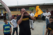 Hector Berrios, general coordinator of MUFRAS-32 and anti-mining activist, leads chants against mining in San Isidro's central park. Pacific Rim's controversial El Dorado gold mine has been the focus of numerous social conflicts at local and national level. Three anti-mining local leaders were murdered in 2009. While a year before, former president Antonio Saca refused to authorize the company's mining permit. This action prompted Pacific Rim to invoked a provision of the Central American Free Trade Agreement (CAFTA) to place the matter in the hands of an international arbitration court. Oceana Gold, who took over Pacific Rim on October 2013 for US $10.2 million , now seeks US $300 million for damages agains the State of El Salvador. San Isidro, Cabañas, El Salvador. September 15, 2014.