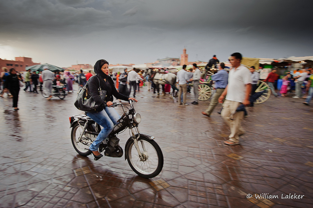 A woman rides a scooter through a rainy Djemaa el-Fna square in Marrakesh, Morocco.