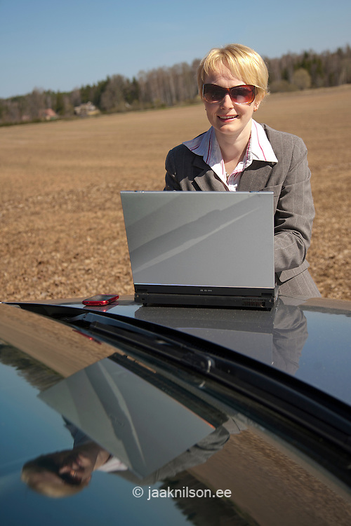 Businesswoman Using Laptop Computer on Car Bonnet by Field