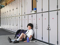 Elementary schoolboy sitting on floor against school lockers portrait