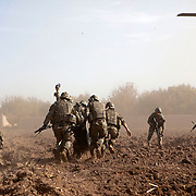 Soldiers of 3 SCOTS (The Black Watch) run across an open field under fire from an insurgent sharpshooter as they CASEVAC a fellow soldier. Private Stephen Bainbridge, aged 25, from Kirkcaldy who was gravely wounded after an IED explosion traumatically amputated his right leg and damaged his left so badly that it too later had to be amputated. His life was saved by the swift actions of Cpl John Goodie (21) a medic with 1 PWRR (The Princess of Wales's Royal Regiment) who applied tourniquets and first field dressings to get the bleeding under control. Private Chis Watson (21) also assisted in the treatment whilst reassuring the casualty and keeping him alert and responsive. Once safely on board the helicopter he was rushed to surgery at Bastion Field Hospital.  Loya Manda, Nad e Ali, Helmand Province, Afghanistan on the 11th of November 2011.