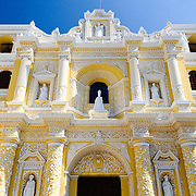 Front of the building of the distinctive  and ornate yellow and white exterior of the Iglesia y Convento de Nuestra Senora de la Merced in downtown Antigua, Guatemala.
