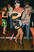 Coquettish masked woman wearing a maids costume posing behind a fan in the dancefloor, Posh at Addington Palace, UK, August, 2004