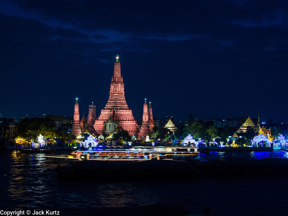 "19 DECEMBER 2013 - BANGKOK, THAILAND:  Wat Arun after the sunset. Wat Arun Ratchawararam Ratchawaramahawihan or Wat Arun (""Temple of Dawn""), a Buddhist temple (wat) in Bangkok Yai district of Bangkok, on the Thonburi side of the Chao Phraya River. The temple derives its name from the Hindu god Aruna, often personified as the radiations of the rising sun. Wat Arun is among the best known of Thailand's landmarks and the first light of the morning reflects off the surface of the temple with pearly iridescence. Although the temple had existed since at least the seventeenth century, its distinctive Khmer style prang (spires) were built in the early nineteenth century during the reign of King Rama II.        PHOTO BY JACK KURTZ"