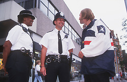 Community police officers talking with teenage boy in street,