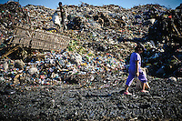 Erni, 10, walking to work at the 'Trash mountain', Makassar, Sulawesi, Indonesia.