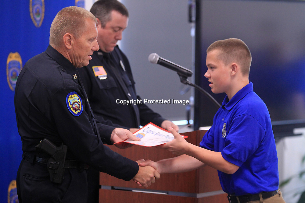 Terry Sanford, Tupelo Police Captain, hands Collier Jones, a graduationg Junior Police Academy Cadet, is graduation certificate at the Junior Police Academy Commencement Ceremony at the Tupelo Police Department Friday morning.